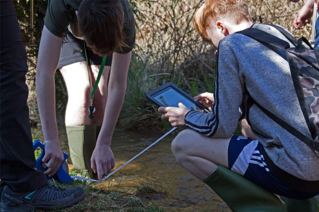 Boys measuring stream and using ipad