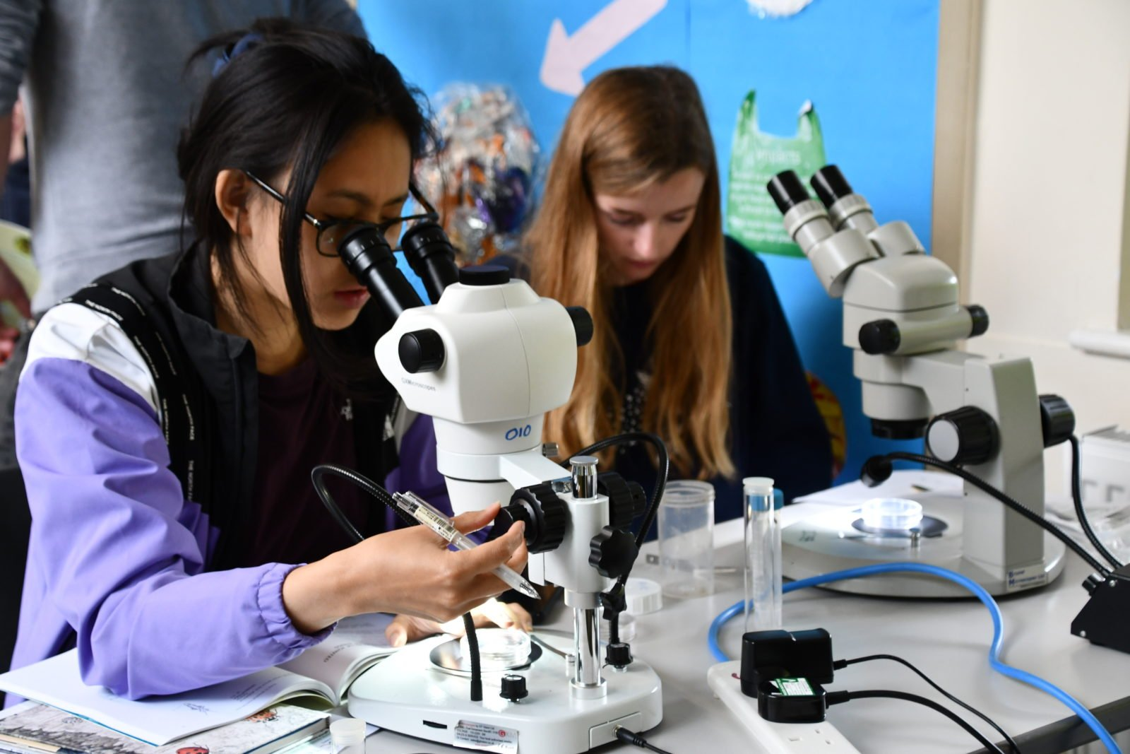 Young people looking in to microscopes
